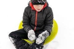 En pojke av sju år gammalt sammanträde på en grön plast- tefatsläde som är klar att rida en glidbana Begrepp av vinteraktiviteter royaltyfri fotografi