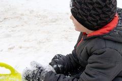 En pojke av sju år gammalt sammanträde på snön och en grön plast- tefatsläde som ligger nära honom Begrepp av vinteraktiviteter, arkivbilder