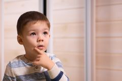 En pojke av tre år gammalt posera framme av kameran på en vit bakgrund arkivbild