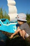 En pojke av två år och ettgjort skepp med en segla på kusten Arkivfoto