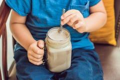En pojke dricker en drink från en carob Royaltyfria Bilder