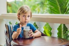 En pojke dricker en drink från en carob Arkivbilder