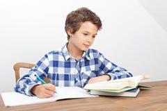 En pojke gör hans läxa Arkivbilder