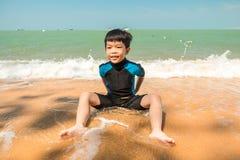 En pojke i baddräkt sitter på stranden och spelar sand royaltyfria foton