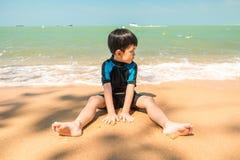 En pojke i baddräkt sitter på stranden och spelar sand fotografering för bildbyråer