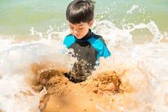En pojke i baddräkt sitter på stranden och spelar sand royaltyfri foto