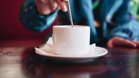 En pojke i ett kafé rör socker i en kopp te close upp Trevliga skott stock video