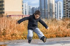 En pojke i ett mörkt omslag hoppar en pöl på vägen arkivfoto