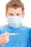 En pojke i ett skyddande maskerar med termometern räcker in Royaltyfri Fotografi