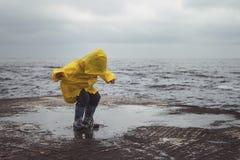 En pojke i gula hopp för en regnrock på pölar royaltyfria foton