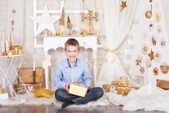 En pojke i guld- julpynt Arkivbilder