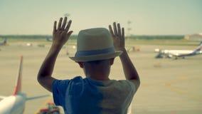 En pojke i en hatt ser nivåer till och med fönstret i flygplatsen stock video