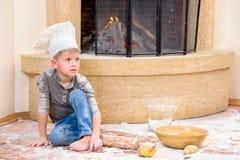 En pojke i hattar för kock` s nära spissammanträdet på kökgolvet som är nedsmutsat med mjöl och att spela med mat som gör röra Arkivfoton