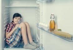 En pojke i en skjorta och kortslutningar som sover inom en kyl royaltyfri fotografi