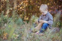 En pojke i träna med en favorit- nallebjörn fotografering för bildbyråer