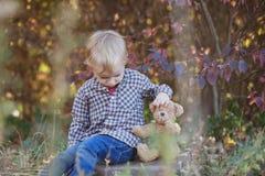 En pojke i träna med en favorit- nallebjörn arkivfoton
