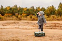 En pojke i underbyxor och ett grått lag står på en gammal resväska i mitt av en sandig landsväg som lyfter hans hand till hans fö Fotografering för Bildbyråer