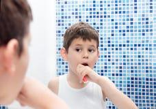 En pojke i en vit T-tröja borstar hans tänder i badrummet Arkivbild