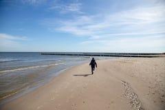 En pojke kör lyckligt på stranden Arkivbild