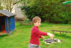 En pojke kastar ett pappers- flygplan i en trädgård Arkivbild