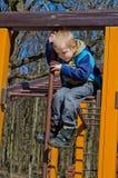 En pojke klättrar på lekplats royaltyfri bild