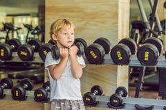 En pojke lyfter upp till, en hantel i idrottshallen arkivfoto
