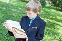 En pojke med en bok i hans hand Pojken läser en bok i den öppna luften Pojken rymmer en bok arkivfoton