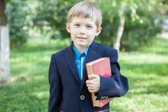 En pojke med en bok i hans hand Pojken läser en bok i den öppna luften Pojken rymmer en bok royaltyfri foto