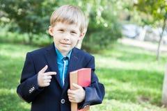 En pojke med en bok i hans hand Pojken läser en bok i den öppna luften Pojken rymmer en bok arkivbilder