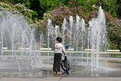 En pojke med en cykel som ser den torra springbrunnen i lilaträdgård i Moskva Arkivfoton