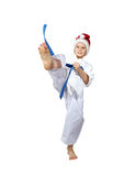 En pojke med ett blått bälte och ett lock av Santa Claus slår ett sparkben Royaltyfri Fotografi