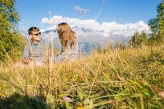 En pojke med en flicka i bergen i bakgrunden av sommarberg av det steniga landskapet med träd sitta på Arkivfoto