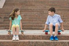 En pojke med en flicka på en bakgrund av en stege som sitter på sportbräden och ser angrily de arkivfoton