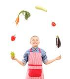 En pojke med förklädet som jonglerar med grönsaker Arkivfoto