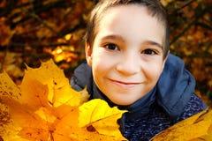 En pojke med lönnlöv i parkera royaltyfri bild