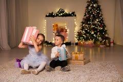 En pojke med ljus för en girland för ferie för nytt år för julklappar för flicka öppna arkivfoto