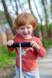 En pojke med ritter för ett leende en sparkcykel arkivbild