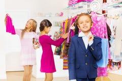 En pojke med shoppingpåsen och flickor väljer kläder Royaltyfri Bild