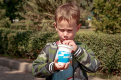 En pojke med yoghurt arkivfoton