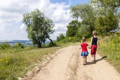 En pojke och barn för en flicka går på en grusväg på en solig sommardag Ungar som tillsammans rymmer händer, medan tycka om ativi royaltyfria foton