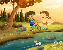 En pojke och en flicka med ett cykelanseende på flodstranden Arkivfoton
