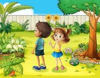 En pojke och en flicka som diskuterar i trädgården Arkivfoto