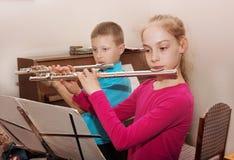 En pojke och en flicka som spelar flöjten arkivfoto