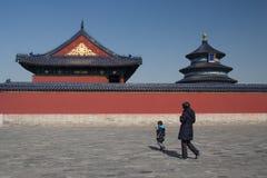 En pojke och en gammal kvinna som förbigår templet av himmel i Peking Royaltyfria Foton