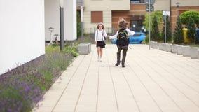 En pojke och en flicka i schoolyarden Flickan går hem, pojkeförsöken att göra hennes skratt, bedrar omkring, kör framåt av henne stock video