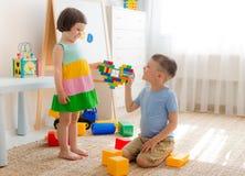 En pojke och en flicka rymmer en hjärta gjord av plast- kvarter Syskongruppen har gyckel som tillsammans spelar i rummet Royaltyfri Bild