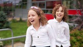 En pojke och en flicka spelar i gården Barnen ser in i avståndet, att vinka och att skratta Lyckligt stock video