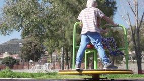 En pojke och en flickaritt i parkerar på en gunga stock video