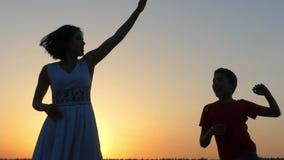 En pojke och en ung kvinna dansar lyckligt på solnedgången lager videofilmer