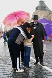 En pojke och vuxna människor möter en person på den röda fyrkanten Arkivfoton
